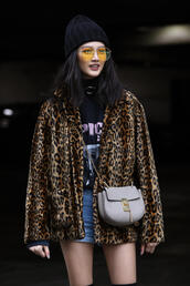 jacket,nyfw 2017,fashion week 2017,fashion week,streetstyle,leopard print,printed jacket,t-shirt,black t-shirt,graphic tee,skirt,mini skirt,blue skirt,denim skirt,bag,grey bag,chain bag,beanie,sunglasses,00s style,yellow sunglasses