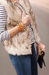 jacket,vest,fur,fur vest,beige fur vest,top,stripes,striped top,bracelets,jewels,jewelry,gold jewelry,gold bracelet,jeans,denim,blue jeans