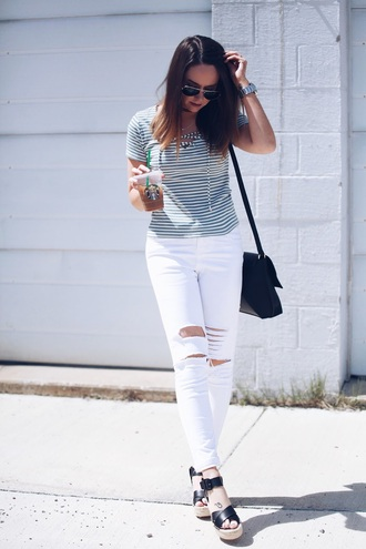 fashionably kay blogger bag sunglasses jewels striped top lace up ripped jeans white jeans black bag shoulder bag wedges white ripped jeans