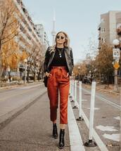 pants,cropped pants,high waisted pants,belt,ankle boots,black boots,black jacket,leather jacket,shoulder bag,round sunglasses,chain necklace