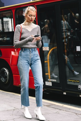 le fashion image blogger sweater bag jeans travel tumblr grey sweater denim blue jeans flare jeans cropped jeans boots mid heel boots ankle boots white boots red bag streetstyle