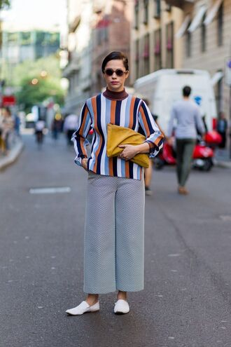 sweater fashion week fashion week street style fashion week 2016 milan fashion week 2016 striped sweater stripes pants wide-leg pants shoes white shoes flats pouch yellow bag bag streetstyle sunglasses