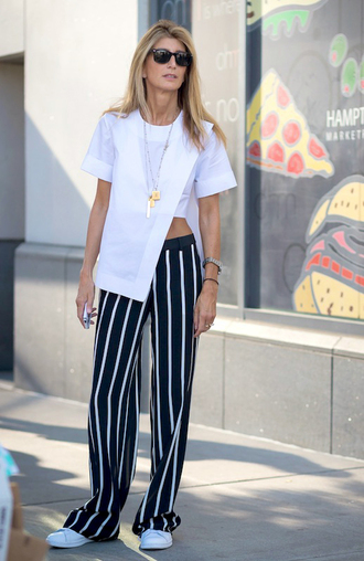 le fashion image blogger sunglasses t-shirt white top asymmetrical black pants stripes black and white white sneakers top asymmetrical top short shorts pants striped pants sneakers spring outfits streetstyle black sunglasses necklace jewels