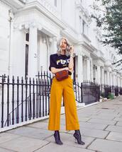 top,black t-shirt,wide-leg pants,yellow pants,fendi,crossbody bag,boots