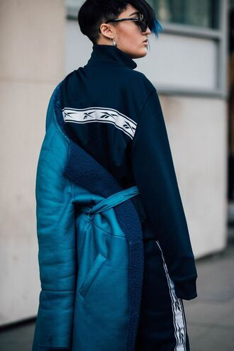 coat london fashion week 2017 fashion week 2017 fashion week streetstyle blue coat top sweatshirt black top pants androgynous non-binary black pants side stripe pants athleisure sunglasses short hair hairstyles