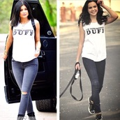 top,duff top,t-shirt,shoes,jeans,distressed denim shorts,graphic tee,shirt,earphones,duff movie,sleeveless top,blouse,tank top,slogan t-shirt,slogan tshirt,ripped jeans,blue jeans,boots,black boots,white,white top,high heels,black,backpack,short hair,amore bracelet,accessories,white tank top,jewels,duff,sleeveless,dress,muscle tee,white t-shirt,black heels,celebrity,bracelets,stacked bracelets,gold bracelet,casual,kylie jenner,model,the duff,i'm someone's duff,mercedes benz