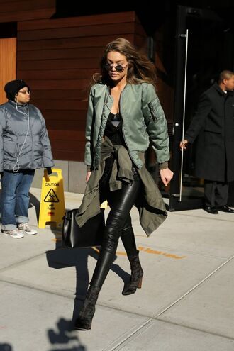jacket round sunglasses green bomber jacket black top black leather pants black boots blogger