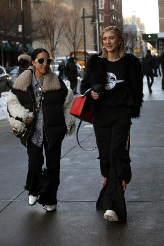 pants nyfw 2017 fashion week 2017 fashion week streetstyle black pants wide-leg pants side stripe pants boots white boots jacket black jacket black fur jacket fur jacket faux fur jacket top black top bag red bag oversized jacket oversized jeans black jeans flare jeans sunglasses shirt striped shirt