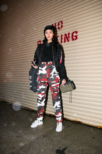pants nyfw 2017 fashion week 2017 fashion week streetstyle camouflage camo pants printed pants top black top jacket black jacket black bomber jacket bomber jacket sneakers white sneakers bag black beanie beanie 00s style