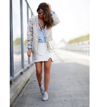 stylista blogger blue shirt white skirt asymmetrical skirt mini bag quilted bomber jacket white bag blue shoes light blue puffer jacket