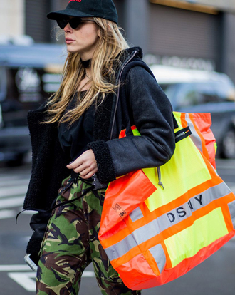 jacket nyfw 2017 fashion week 2017 fashion week streetstyle black jacket shearling jacket black shearling jacket bag orange pants green pants khaki khaki pants camouflage camo pants sunglasses cap ny fashion week 2017