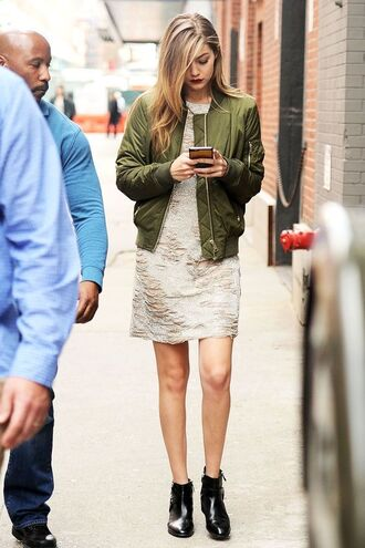 jacket gigi hadid bomber jacket bomber jacket satin bomber green bomber jacket green jacket dress boots ankle boots black boots gigi hadid gigi hadid style celebrity celebrity style streetstyle model off-duty white dress mini dress