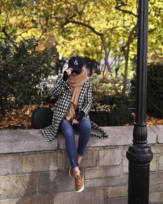 coat cap tumblr printed coat checkered denim jeans blue jeans skinny jeans sneakers beige sneakers bag black bag round bag scarf camel