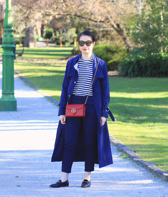 an odd girl blogger coat top pants bag shoes sunglasses gucci bag red bag crossbody bag trench coat blue coat fall outfits loafers blue pants striped top