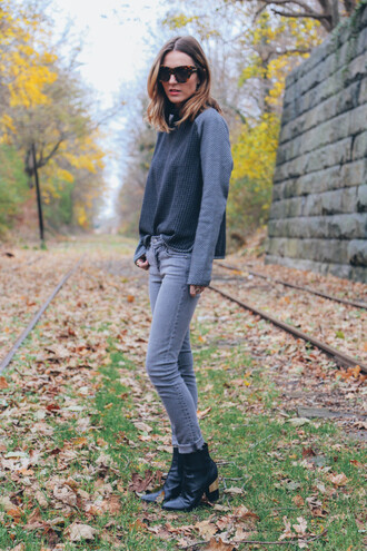 blogger sunglasses grey sweater prosecco and plaid grey jeans cat eye