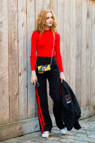 top fashion week street style fashion week 2016 fashion week paris fashion week 2016 red top long sleeves pants wide-leg pants bomber jacket black bomber jacket black jacket jacket bag printed bag streetstyle red sweater sporty chic athleisure side stripe pants