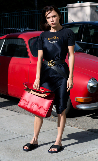 always judging blogger slip dress silk dress slide shoes gucci bag red bag black top black shirt graphic tee black dress gucci waist belt black flats black slides dress over t-shirt black t-shirt t-shirt handbag silk slip dress gucci belt