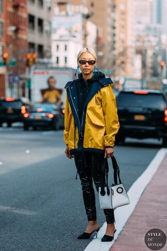 jacket yellow jacket pants black pants vinyl shoes black shoes mules sunglasses bag white bag