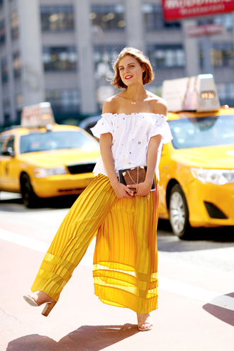 pants off the shoulder cold shoulder cold shoulder top off the shoulder top white top yellow pants wide-leg pants pleated pants clutch brown clutch high heel sandals nude sandals streetstyle chic