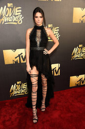 kendall jenner,mtv movie awards,red carpet,red carpet dress,asymmetrical dress,high-low dresses,black dress,black,gown,prom dress,kardashians,sexy dress,backless dress,backless,lace up heels