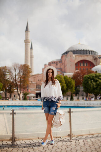 the bow-tie blogger top shirt shoes hat three-quarter sleeves white top off the shoulder off the shoulder top white hat sun hat backpack white backpack shorts denim shorts blue shorts slip on shoes blue shoes printed slippers