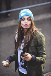 jacket,cara delevingne,beanie,hat,army green jacket,cara delevinge,green,blue hat,model,blonde hair,victoria's secret,eyebrows,candace,robe,silky,vs,clouds,model off-duty