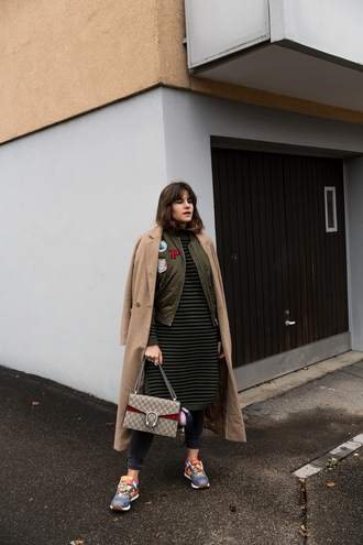 the fashion fraction blogger jeans bomber jacket green bomber jacket beige coat winter outfits sneakers gucci bag long coat bright sneakers striped dress printed knit dress camel long coat