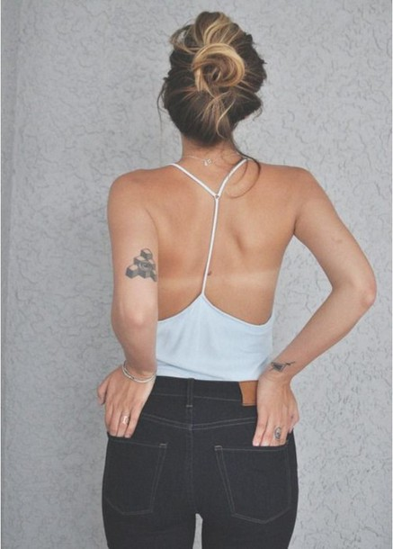 blouse cute style jeans jewels black jeans blonde hair tank top tattoo bun pants dark jeans dark pants white top high waisted jeans top grey backless top blue racerback