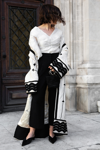 coat black and white caftan caftan black pants black trousers wide-leg pants white top white shirt v neck black shoes pointy flats
