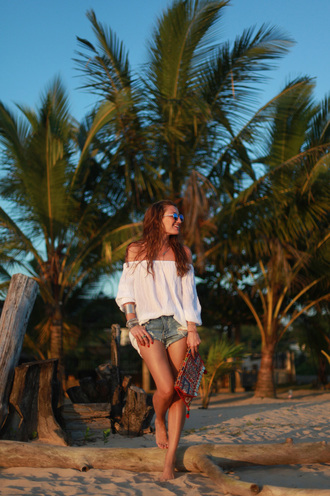 b a r t a b a c blogger sunglasses off the shoulder summer outfits denim shorts top shorts bag jewels white off shoulder top off the shoulder top bracelets cuff bracelet embellished bag embellished printed clutch summer top blue shorts puffed sleeves