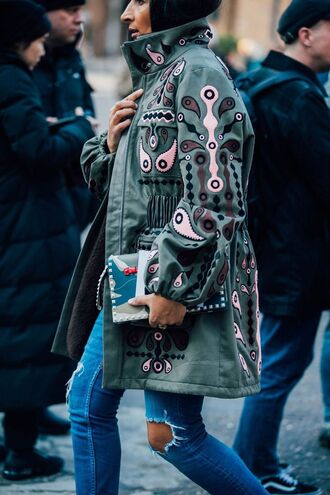 coat london fashion week 2017 fashion week 2017 fashion week streetstyle green coat embroidered bag printed bag denim jeans blue jeans ripped jeans