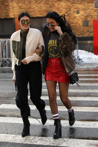 skirt tumblr mini skirt nyfw 2017 fashion week 2017 fashion week streetstyle red skirt vinyl leather skirt tights net tights fishnet tights jacket fur jacket faux fur jacket brown jacket brown bag tassel boots black boots ankle boots high heels boots socks t-shirt logo tee pants black pants top white jacket sunglasses mirrored sunglasses round sunglasses 00s style