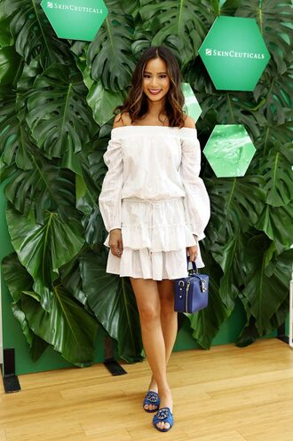 dress sandals purse summer dress summer outfits ruffle ruffle dress jamie chung blouse blogger white white dress shoes off the shoulder off the shoulder dress mini dress short dress blue bag celebrities in white celebrity style slide shoes blue slides