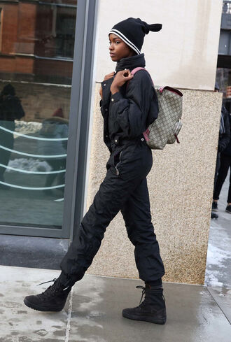 jumpsuit nyfw 2017 fashion week 2017 fashion week streetstyle black overalls overalls black jumpsuit boots black boots winter outfits winter look flat boots winter boots backpack beanie black beanie