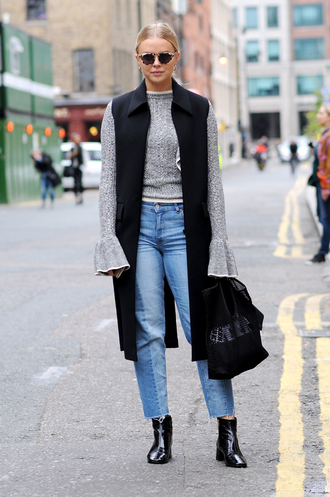 sunglasses fashion week street style fashion week 2016 fashion week london fashion week 2016 grey sweater ruffle bell sleeves jeans patchwork blue jeans denim cropped jeans vest black vest boots ankle boots mid heel boots streetstyle fall outfits bell sleeve sweater ruffle sweater
