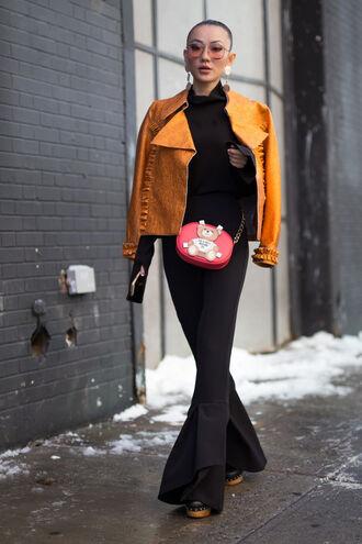 jacket nyfw 2017 fashion week 2017 fashion week streetstyle orange leather jacket top black top pants black pants flare pants bag red bag sunglasses 00s style