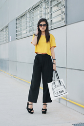 fake leather,t-shirt,sunglasses,bag,pants,shoes,yellow t-shirt,crop tops,wide-leg pants,black pants,quote on it,sandals,wedge sandals,black sandals,tortoise shell