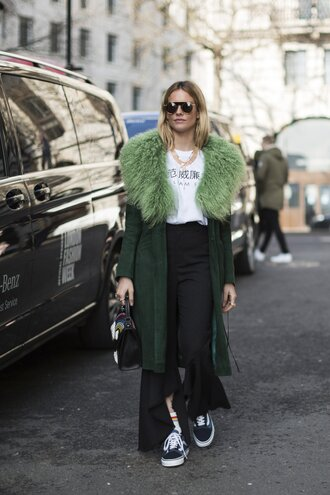 coat london fashion week 2017 fashion week 2017 fashion week streetstyle green coat fur collar coat t-shirt white t-shirt logo tee necklace accessories accessory jewels jewelry sunglasses pants black pants kick flare asymmetrical sneakers blue sneakers vans socks vans outfits bag