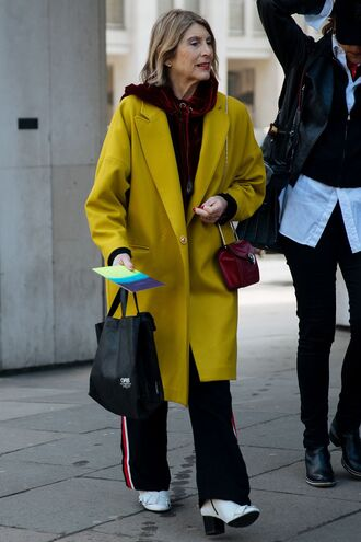 coat london fashion week 2017 fashion week 2017 fashion week streetstyle yellow yellow coat hoodie velvet velvet top burgundy top pants black pants side stripe pants boots white boots bag red bag bulgari serpenti bag