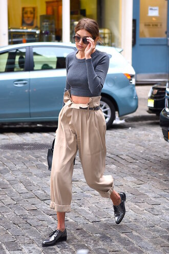pants capri pants gigi hadid celebrity style celebrity model cream pants high waisted pants top crop tops grey top long sleeve crop top long sleeves shoes oxfords silver shoes sunglasses bag black bag