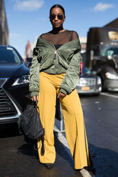 pants,nyfw 2017,fashion week 2017,fashion week,streetstyle,yellow,wide-leg pants,jacket,bomber jacket,green bomber jacket,khaki bomber jacket,army green jacket,top,black top,see through,see through top,backpack,black backpack,sunglasses