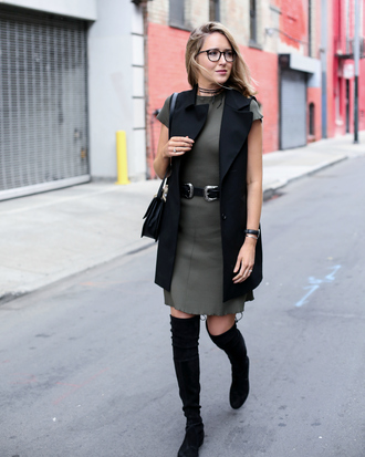 the classy cubicle blogger belt jewels knee high boots suede boots sleeveless long coat black bag double buckle belt black belt green dress short dress vest black vest long vest glasses nerd glasses over the knee boots over the knee fall outfits flat boots black choker shoulder bag