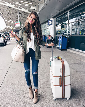 southern curls and pearls blogger jacket jewels bag white top white bag ripped jeans skinny jeans green jacket suede boots airport fashion suitcase cuffed jeans blue jeans ankle boots high heels boots nude boots