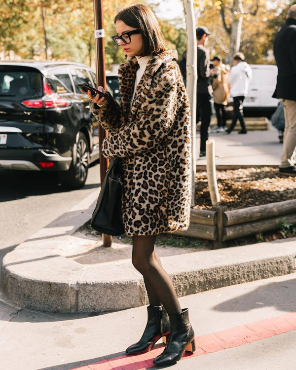 coat leopard print turtleneck mini skirt booties mid heel boots tights handbag glasses