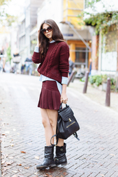 the golden diamonds,blogger,pleated skirt,mini skirt,burgundy,burgundy skirt,burgundy sweater,knitted sweater,fall outfits,striped shirt,leather backpack,back to school,black backpack,black boots,flat boots,cat eye,red cable knit sweater