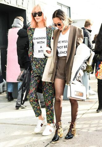 t-shirt nyfw 2017 fashion week 2017 fashion week streetstyle equality feminist quote on it white t-shirt blazer grey blazer shorts tights boots lace up boots ankle boots bag white bag pants printed pants printed blazer sneakers gucci shoes gucci white sneakers low top sneakers sunglasses black sunglasses jacket black jacket feminist tshirt