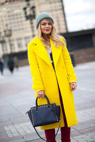 coat yellow coat black bag burgundy jeans blogger