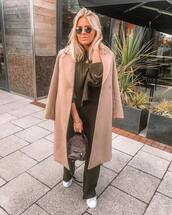 bag,leather backpack,pink coat,pants,brown sweater,white sneakers,gold necklace,sunglasses