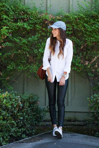 hat blue cap white shirt leather pants white sneakers brown handbag blogger