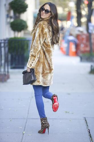 something navy blogger jeans louboutin leopard print high heels winter outfits cat eye pouch winter coat faux fur printed boots printed ankle boots high heels boots boots animal print animal print high heels leopard print fur coat black sunglasses sunglasses bag black bag blue jeans beige fluffy coat fuzzy coat